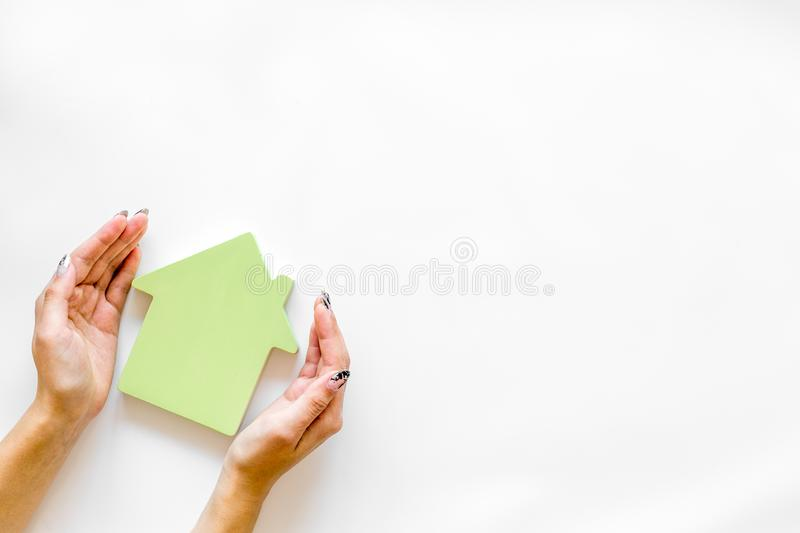 Buy house with house figure in hands on office desk white background top view mock-up. Property insurance concept. Buy house with house figure in hands on office stock photo