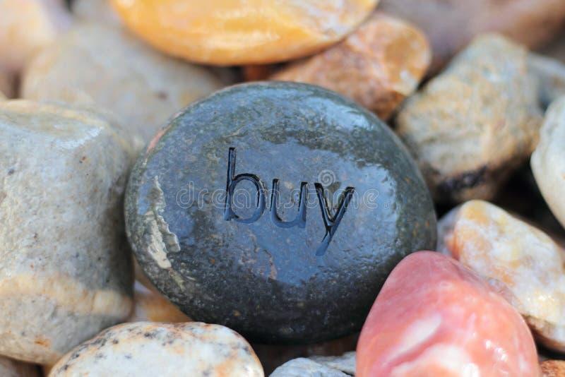 Buy. Imprinted on wet stones stock image