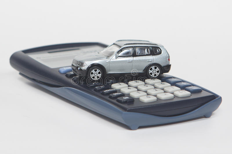 Buy a new car. Calculator and toy car isolated on white background stock images