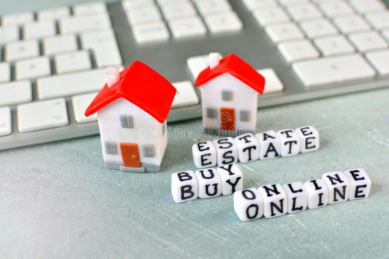 Buy real estate online concept with miniature house, computer keyboard and cubes with letters. royalty free stock photos