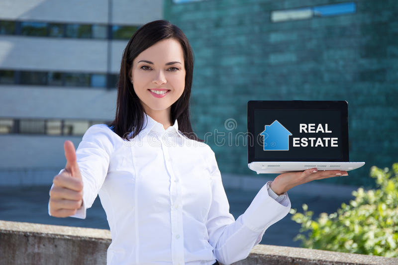 Buy or rent - beautiful business woman holding laptop with real. Estate application and thumbs up stock photo