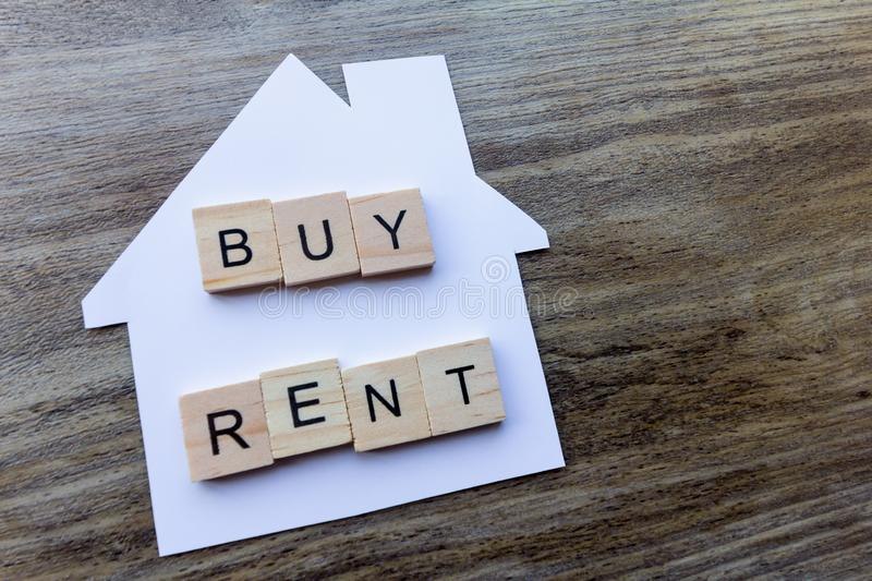 Buy, Rent - Housing Market Concept. Housing Market Concept - Paper house with the words `Buy, Rent stock photography