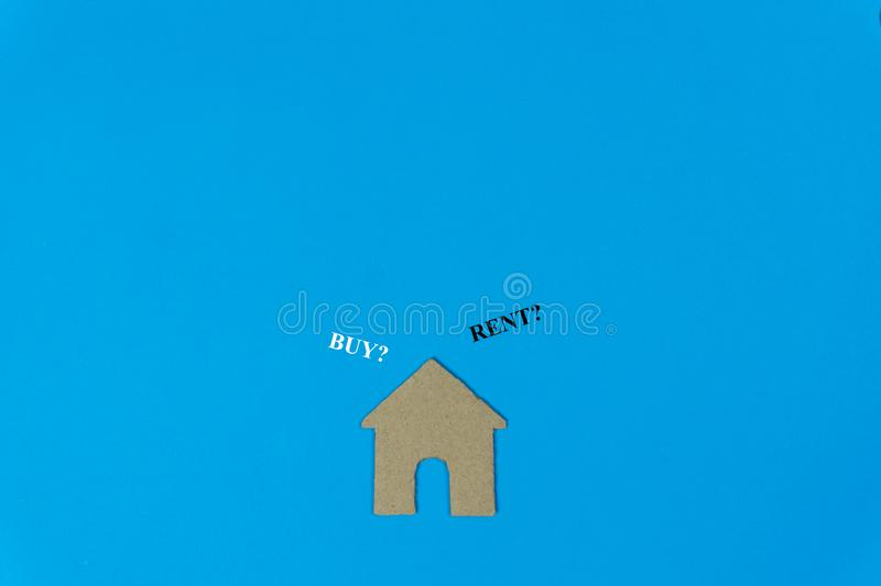 Buy or rent. A small house model made by paper cut on blue background with text.  stock photos