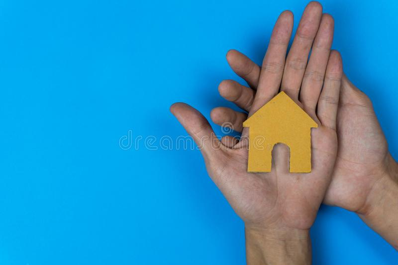 Buy or rent. A small house model made by paper cut on a man hand on  blue background.  stock image