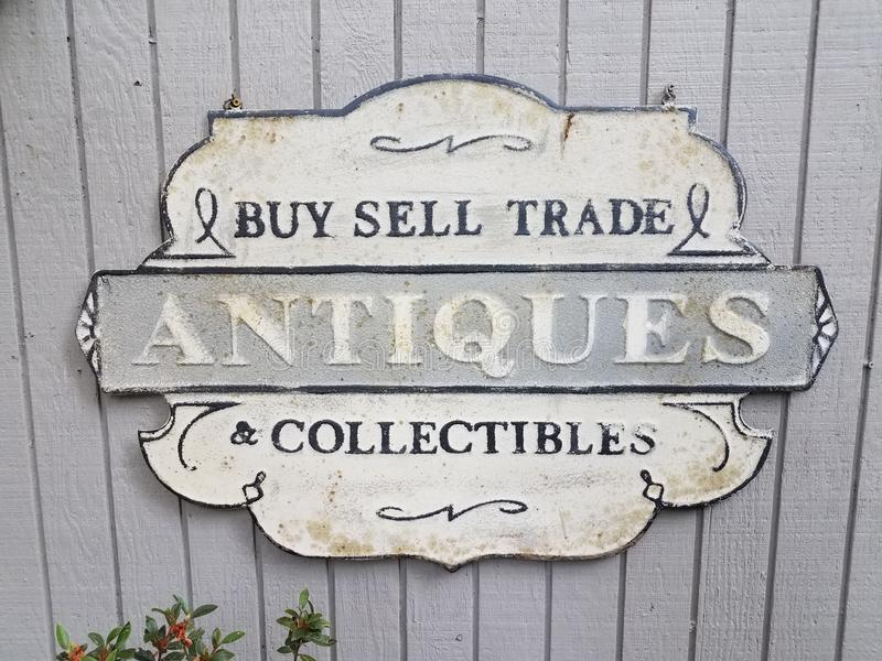 Buy sell trade antiques collectibles sign on grey wall. Old buy sell trade antiques collectibles sign on grey wall royalty free stock photography
