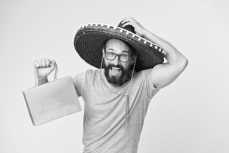Buy souvenir from travel. Man wear sombrero hat shopping yellow background. Guy with beard happy in sombrero. Souvenir. Gift from abroad. Man hold shopping bag stock image