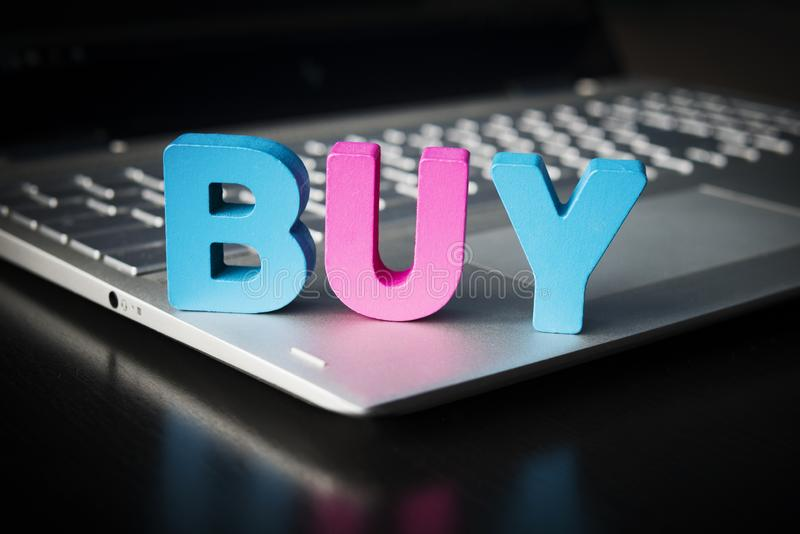 Buy word on laptop bottom at black background. Wooden colorful letters B, U, Y set on opened notebook. Concept of buying things in. Internet. Online shopping royalty free stock photos