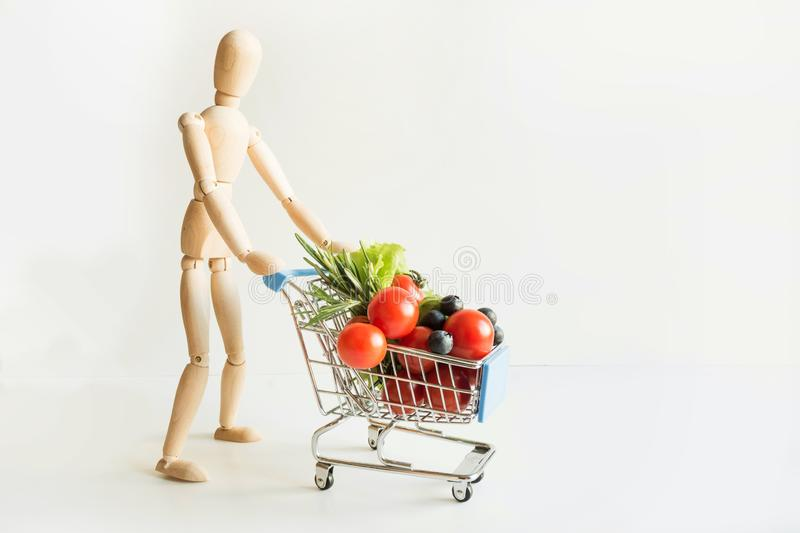 Buyer as dolls with grocery trolley. Full food basket. Concept shopping stock photography