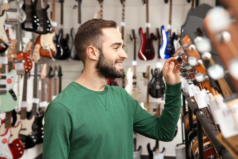 Buyer choosing guitar in music store. Buyer choosing guitar in modern music store royalty free stock photography