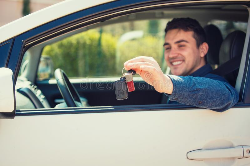 Buyer sitting in his new vehicle, auto purchase, rental business concept. Positive smiling young man driver showing car keys out window. Car sale, rental royalty free stock photography