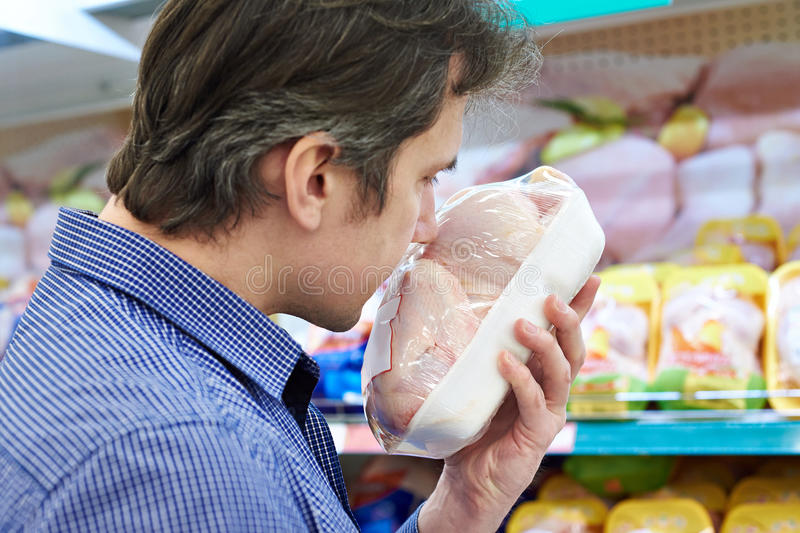 Buyer sniffing chicken in store, checking freshness stock images
