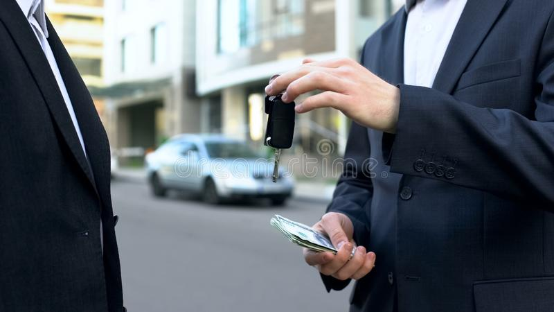 Buyer of vehicle paying money to auto owner, sale of car without intermediary. Stock photo stock photography