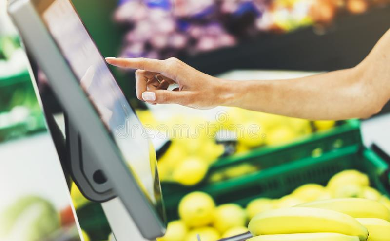 The buyer weighs the yellow bananas and points the fingers on the screen electronic scales, woman shopping healthy food in super. Market blur background, female royalty free stock images