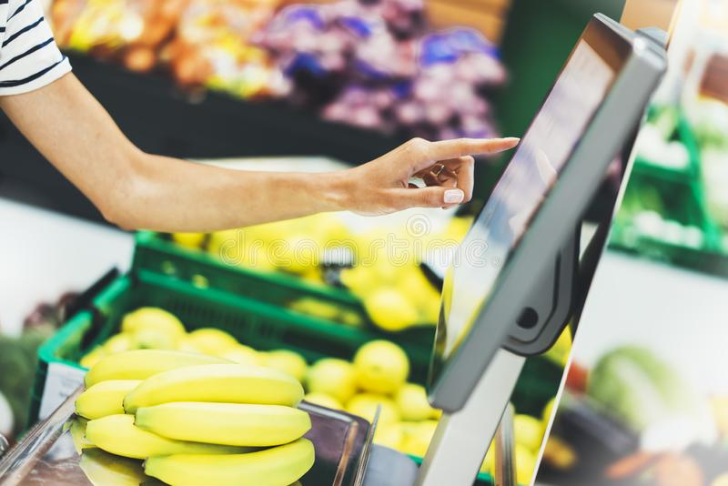 The buyer weighs the yellow bananas and points the fingers on the screen electronic scales, woman shopping healthy food in super. Market blur background, female royalty free stock image