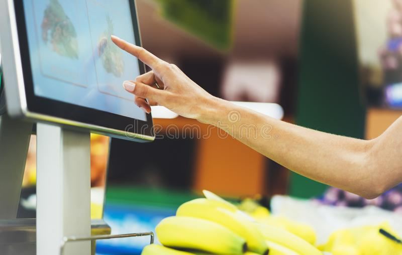 The buyer weighs the yellow bananas and points the fingers on the screen electronic scales, woman shopping healthy food. In supermarket blur background, female royalty free stock image