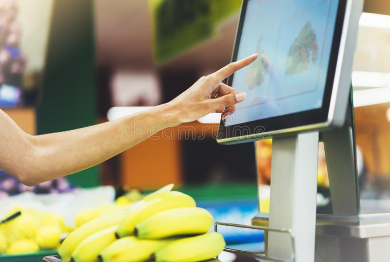 The buyer weighs the yellow bananas and points the fingers on the screen electronic scales, woman shopping healthy food. In supermarket blur background, female royalty free stock photography