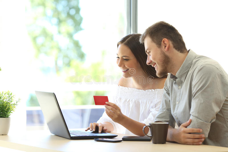 Buyers buying online with credit card. Couple of buyers buying on line with credit card and a laptop at home or hotel royalty free stock image