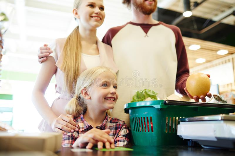 Buyers in hypermarket. Happy family of three standing by cash-register in modern hypermarket stock images