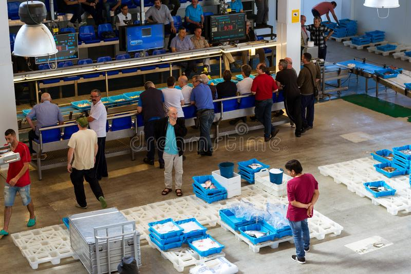 Buyers traded at conveyor, fish auction in Blanes. Blanes, Spain - 31 may, 2018: Buyers are traded at conveyor. Fish auction for wholesalers and restaurants royalty free stock photo