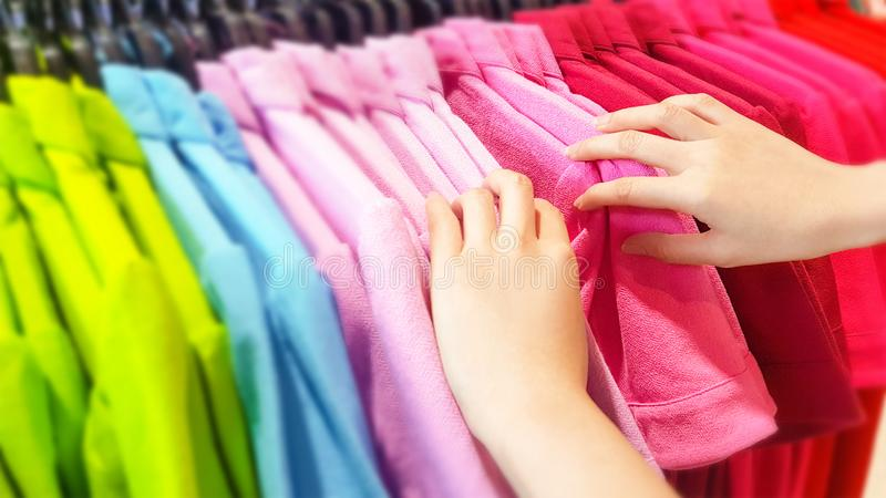 Buying Clothes in A Shopping Mall Store. Close Up of Woman Hand Choosing and Discount Colorful T-Shirt on Hanger in Store. People royalty free stock photo