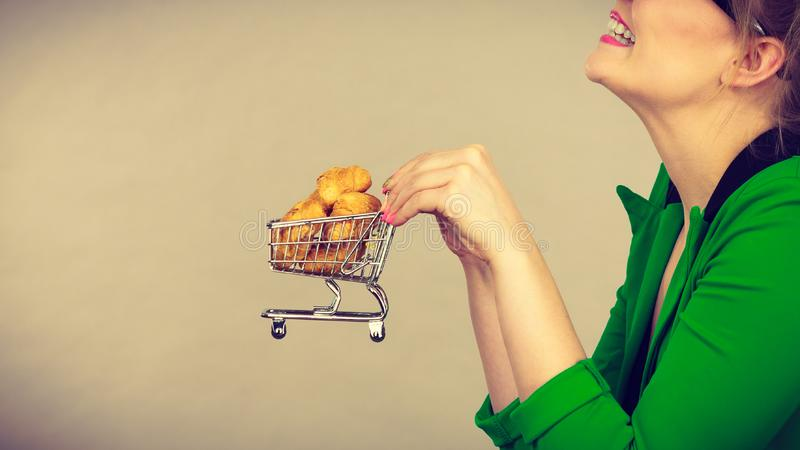Woman hand holding shopping cart with bread stock image