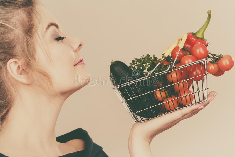 Woman holds shopping basket with vegetables, smelling stock photography