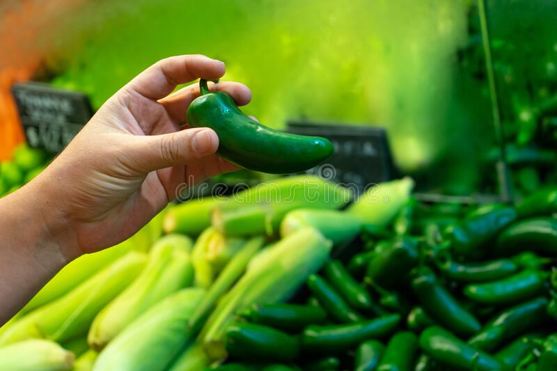Buying jalapenos peppers. Buying green jalapenos chili peppers stock photos