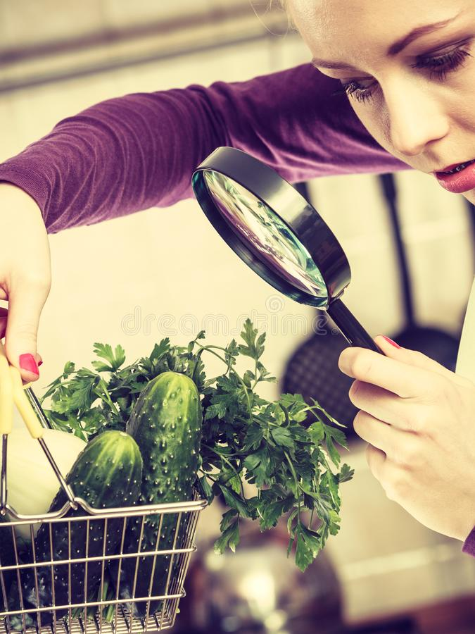 Woman looking through magnifier at vegetables basket royalty free stock photo