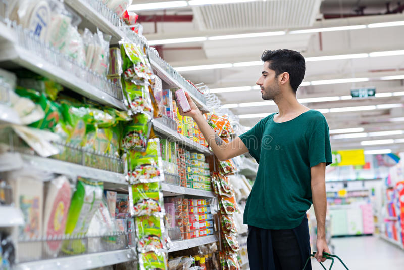 Buying instant food. Handsome young man buying instant food in the supermarket royalty free stock images