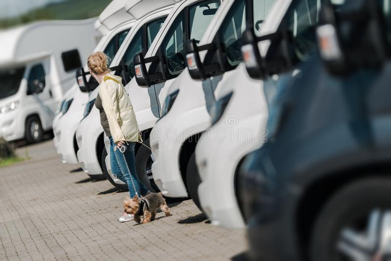Buying New Camper Van. Caucasian Woman Buying New Camper Van. Looking Around To Find the Perfect Camper on the Dealership Lot stock photo