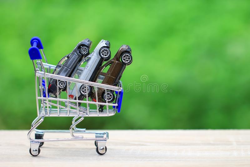 Buying new car concept, Miniature car model in Shopping cart on nature green background stock photos