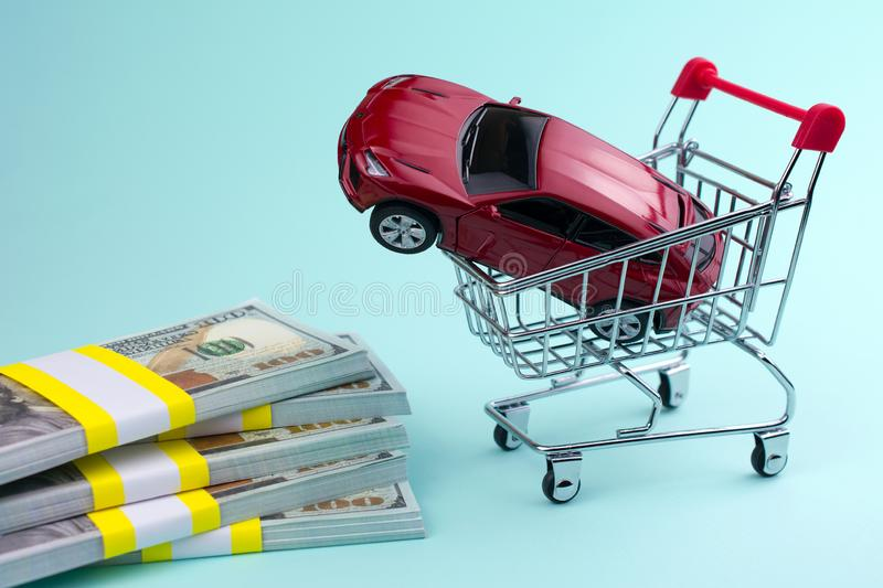 Buying a new car concept. red car money shopping cart stock photography