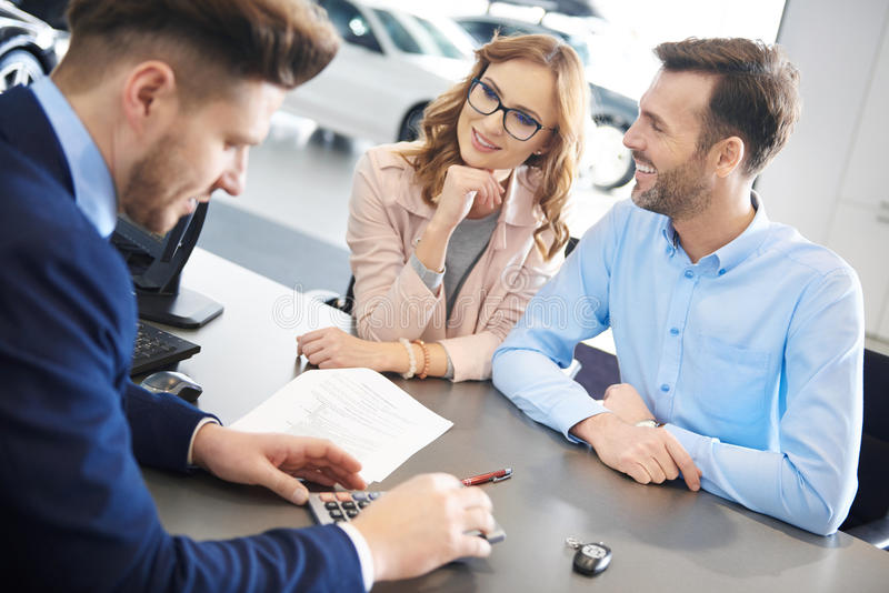 Buying new car by couple stock photography