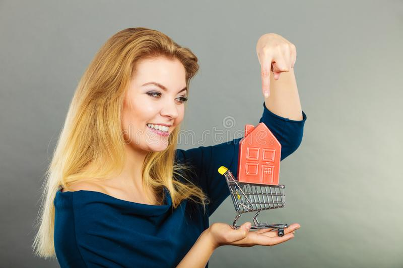 Woman holding shopping cart with house inside stock photography