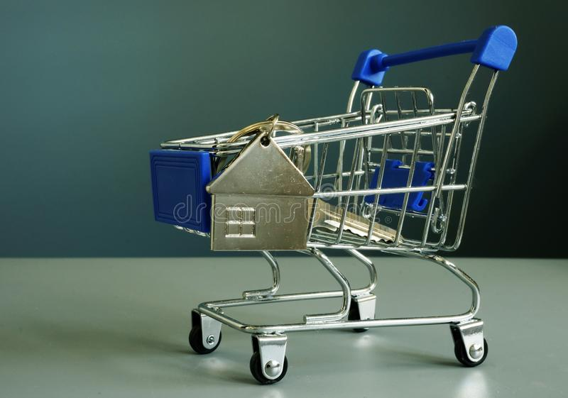 Buying property. Shopping cart and key for house. royalty free stock images