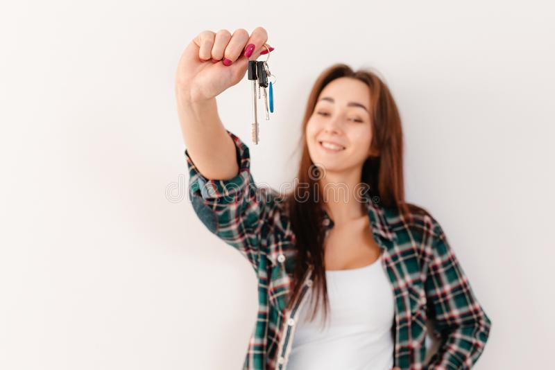 Buying and renting real estate. A smiling woman in a plaid shirt holds a bunch of keys. Hand with keys in focus, close stock photo