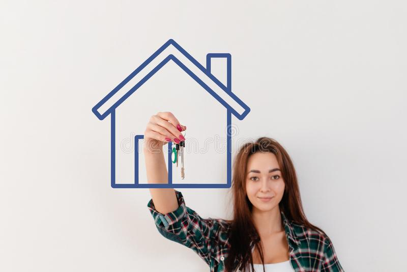 Buying and renting real estate. A woman in a plaid shirt holds a bunch of keys, in a painted blue house. Hand in focus stock photography