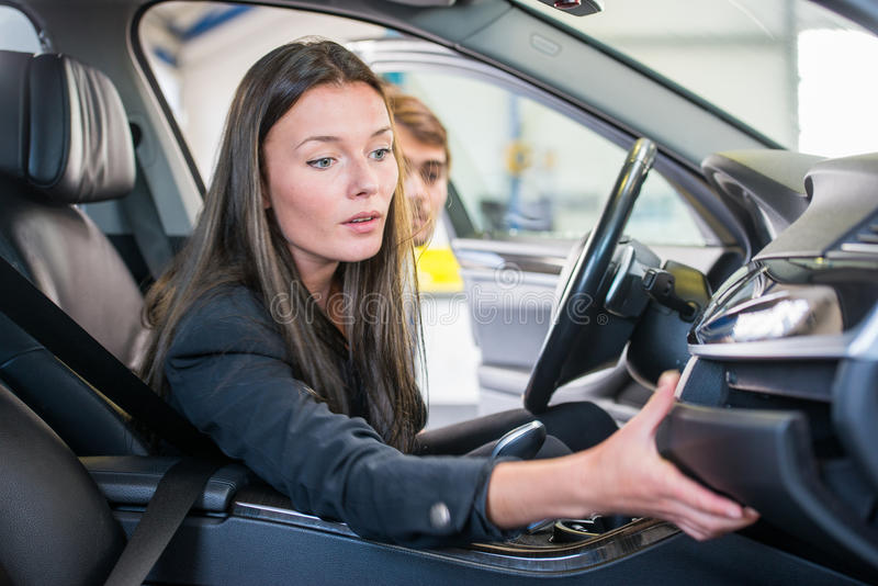 Buying a second hand car. Young woman, reaching for the glove compartment at a garage, looking to buy a second hand car stock image