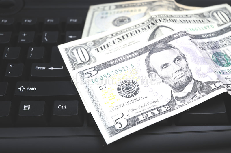 Buying and selling through the internet. Some Dollar banknotes lying on a keybord royalty free stock photos