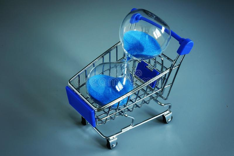 Buying some time for yourself. Shopping cart and sand clock stock images