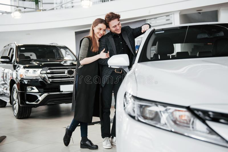 Buying their first car together. High angle view of young car salesman standing at the dealership telling about the. Features of the car to the customers royalty free stock images