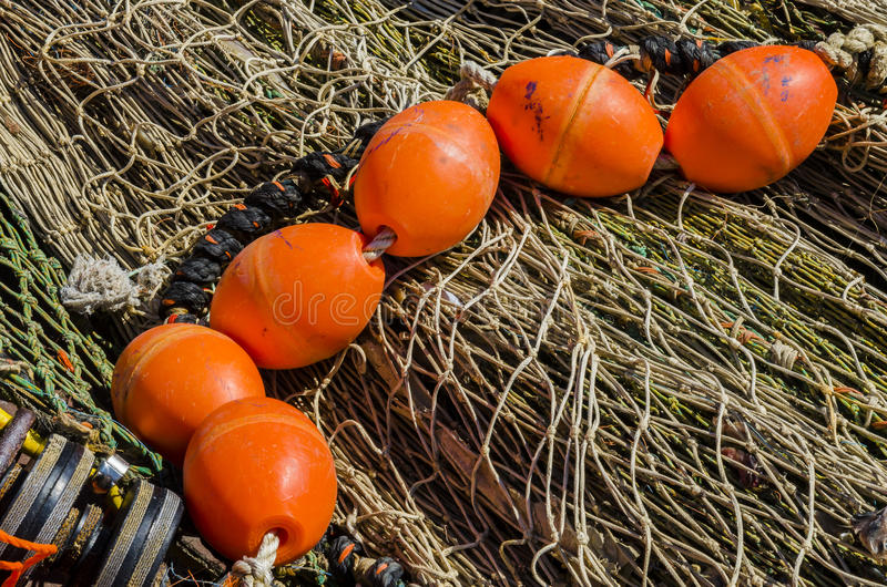 Buyo on Nets. A pile of grey fishing nets and on top several orange buoys in the harbour of Urk, Flevoland, The Netherlands royalty free stock photo