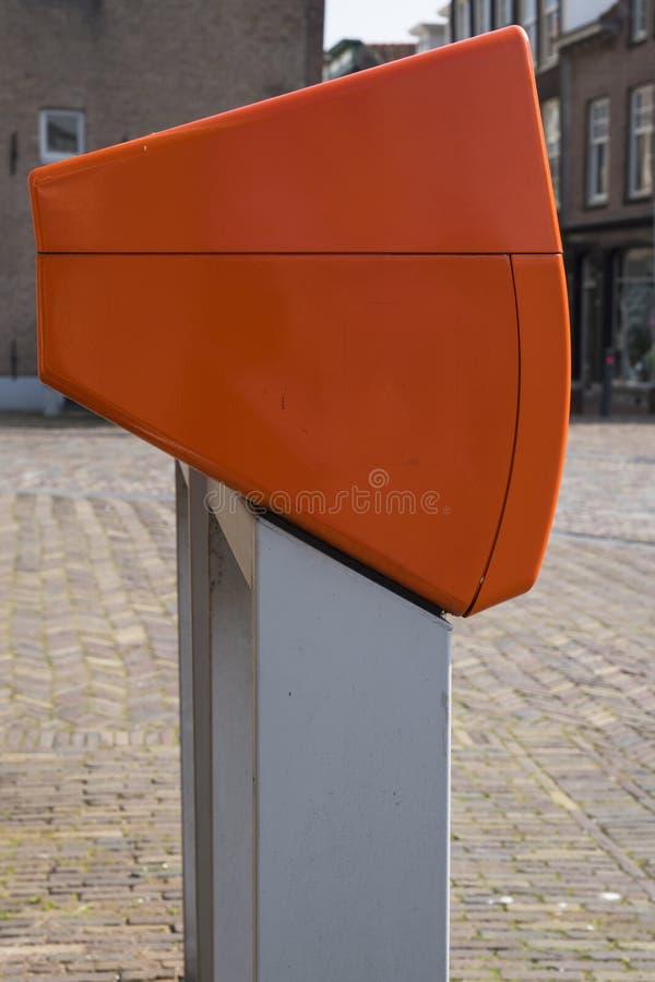 Buzón anaranjado holandés típico en calle foto de archivo