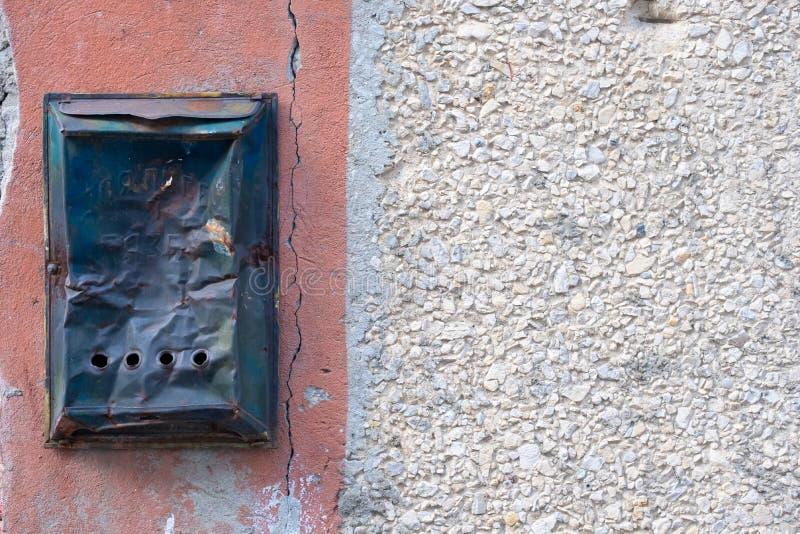 Buzón arrugado viejo en un muro de cemento Estilo retro fotografía de archivo