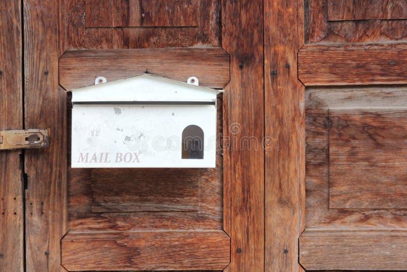 Buzón blanco en puerta de madera vieja imagen de archivo