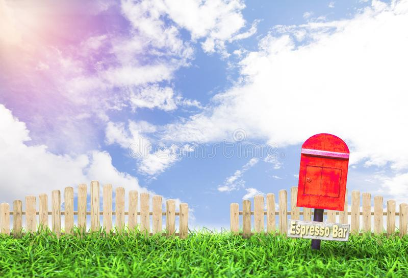 Buzón de correos y de madera rojos en jardín con la valla de estacas y el cielo de la falta de definición en el día foto de archivo