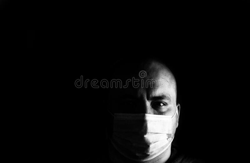 BW photo of sick young man with medical protective face mask illustrates pandemic coronavirus, Covid 19 disease isolated on black. Copy space. Covid-19 outbreak stock images