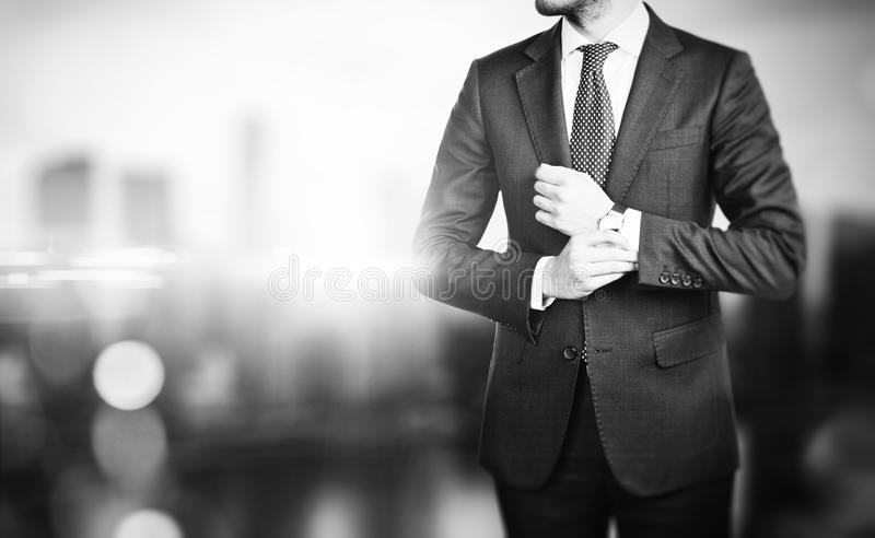 BW picture of young business man on a blured. Black and white picture of young businessman touching his watch and the city on the blured background royalty free stock photo