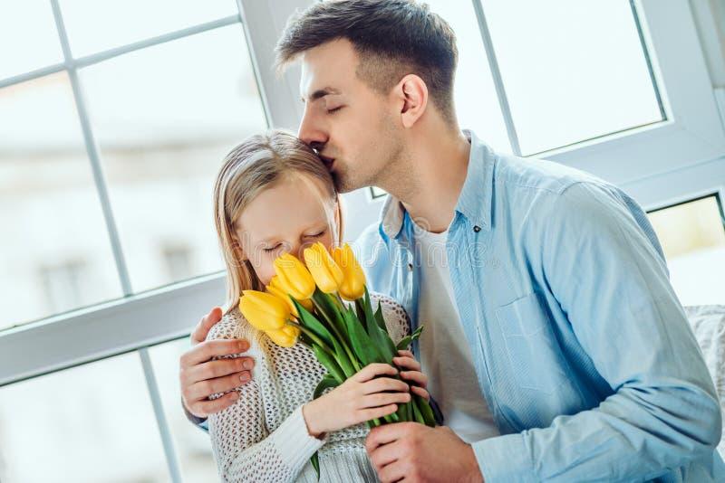 Być z ojczulkiem jest bestDaughter siedzi wpólnie na windowsill w domu ojcem i Małego dziecka mienia bukiet tulipany zdjęcia stock