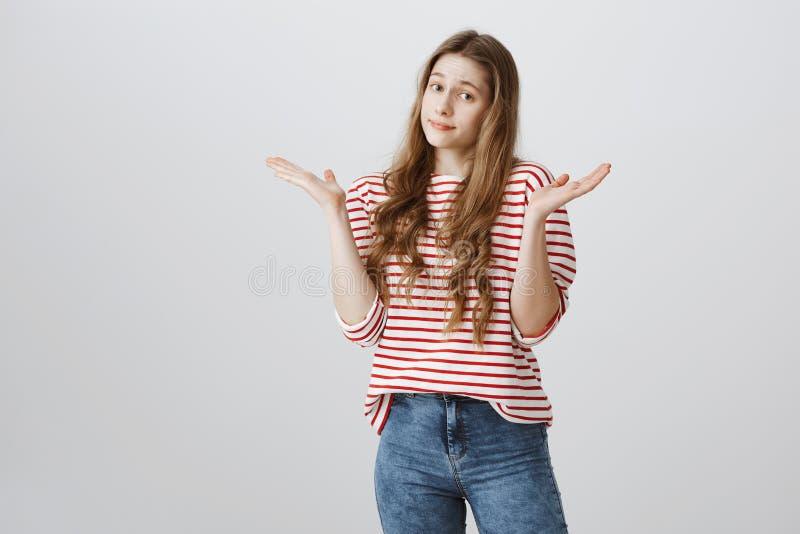 Być może znasz odpowiedzi przyczynę ty ona nieświadoma Portret zmieszana nieświadoma młoda kobieta wzrusza ramionami z nastroszon fotografia stock